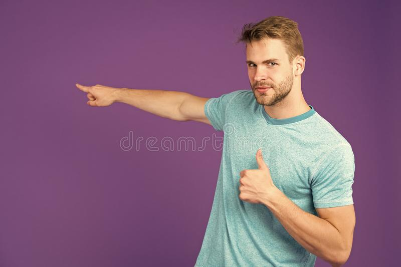 Highly recommend pointing at with index finger. Man unshaven face shows thumbs up gesture violet background. Man. Satisfied face recommend show right direction stock photography