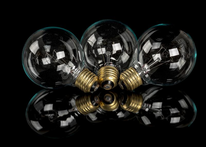 Three Glass incandescent light bulbs laying on a black table stock photo