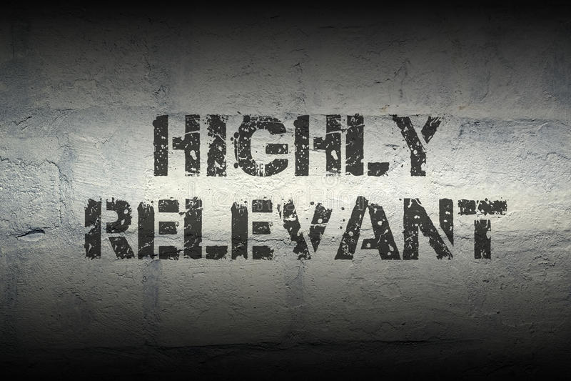 Highly relevant gr. Highly relevant stencil print on the grunge white brick wall; specially designed font is used royalty free stock photography