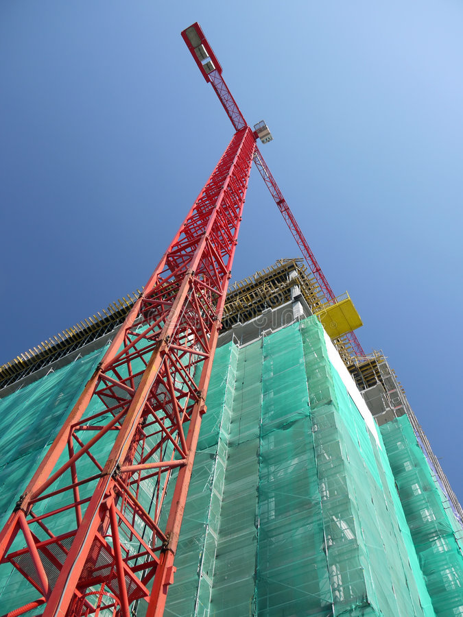Highrise construction. Raw state residential highrise and jib crane over clear blue sky stock images