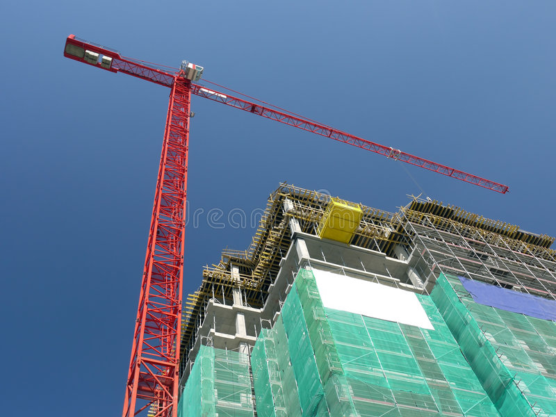 Highrise construction. Raw state residential highrise and jib crane over clear blue sky stock image