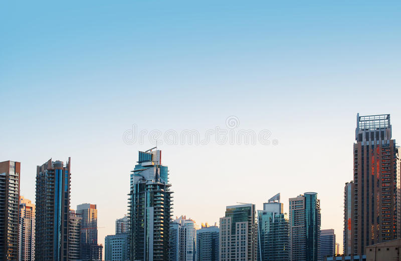 Highrise glass skyscraper buildings skyline in blue dominant against a partially clouded sky.  royalty free stock photos