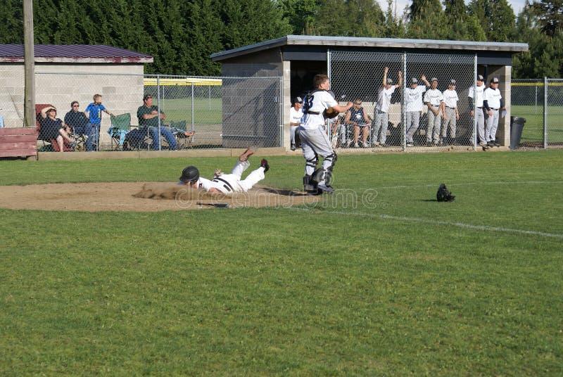Highschool Baseball-Spieler, der Schmutz isst stockfotos