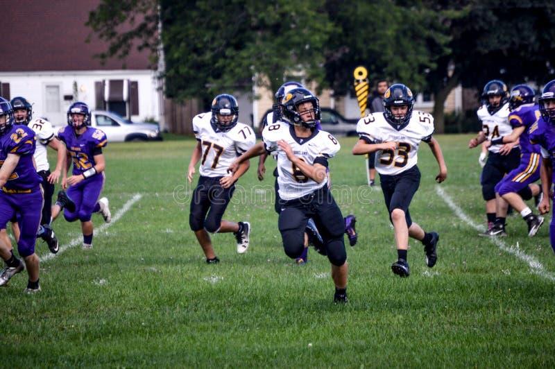 Highschool Fußball-Spieler, die in Richtung zum Ball laufen stockbilder