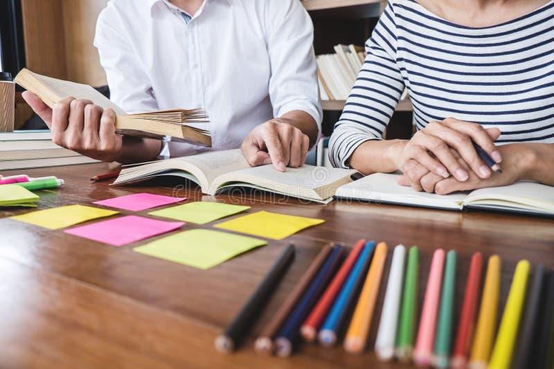 Highschool oder Studentgruppe, die am Schreibtisch in der Bibliothek sitzt stockfotografie