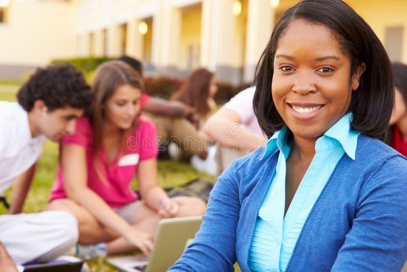 Highschoollehrer-Sitting Outdoors With-Studenten auf dem Campus stockfoto