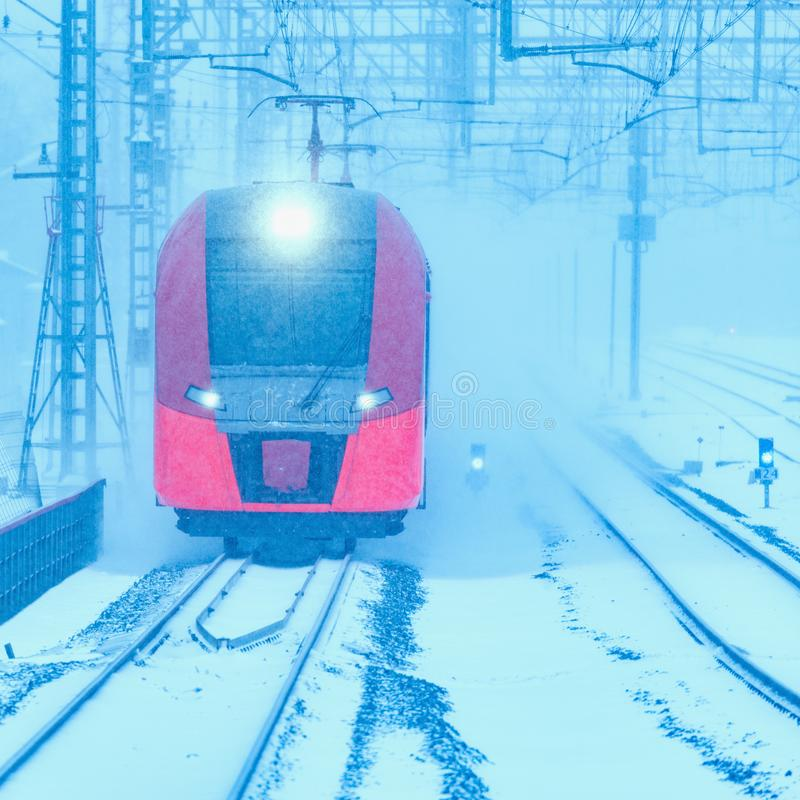 Highspeed train approaches to station platform. Highspeed train approaches to the station platform at cold snowstormy day time stock image