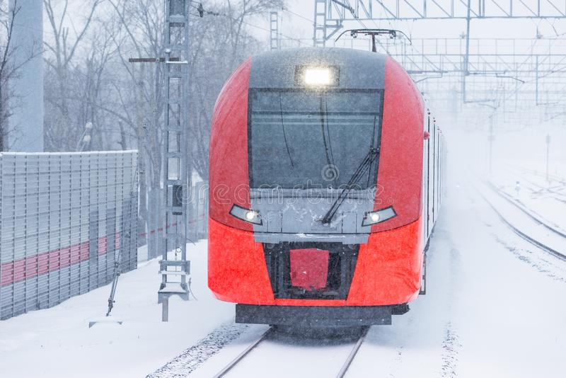 Highspeed train approaches to the station platform. Highspeed train approaches to the station platform at snowstormy day time stock photos