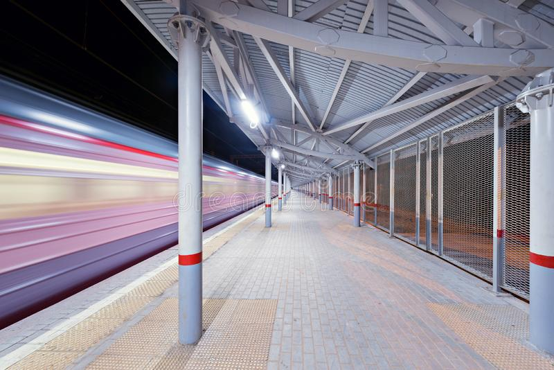 Highspeed train arrives to the station platform. Highspeed train arrives to the station platform at night time stock image