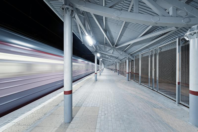 Highspeed train arrives to the station platform. At night time stock photos