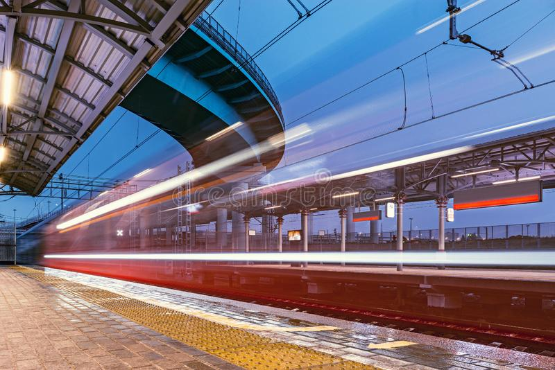 Highspeed train arrives to the station platform. Highspeed train arrives to the station platform at rainy evening time stock photo