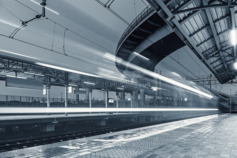 Highspeed train arrives to the station platform. Highspeed train arrives to the station platform at rainy evening time stock image