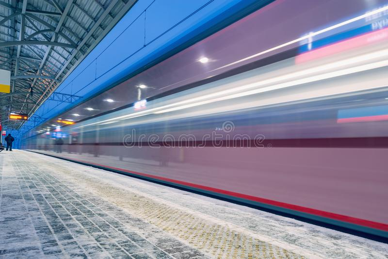 Highspeed train arrives to the station platform. Highspeed train arrives to the station platform at winter evening time royalty free stock photo