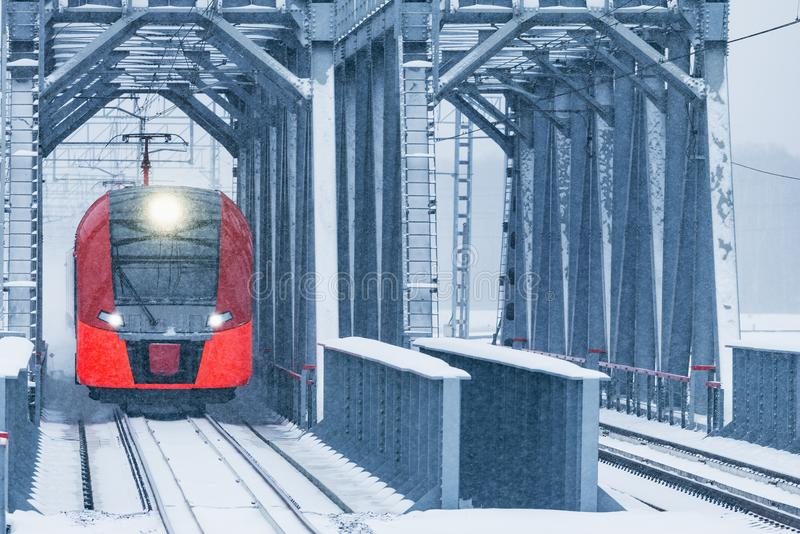 Highspeed train moves through the bridge. Highspeed train moves through the bridge at snowstormy day time royalty free stock image