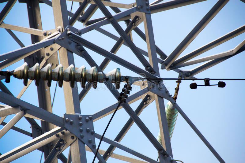 Highvoltage insulator and a fragment of electricity pylon metal. Construction close up. Selective focus stock image
