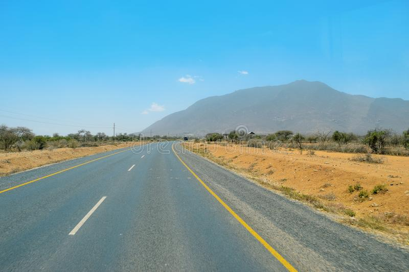 Highway against a mountain background, Tanzania. Highway on our way to Arusha Town, Tanzania royalty free stock photography