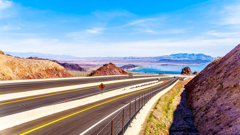 Highway 93 as it dips down to the Mike O` Callaghan-Pat Tillman Memorial Bridge over the Colorado River at the Hoover Dam stock images