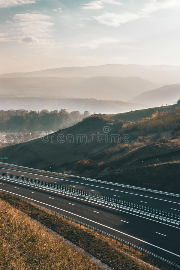 Highway with a beautiful sunset and mountains royalty free stock images