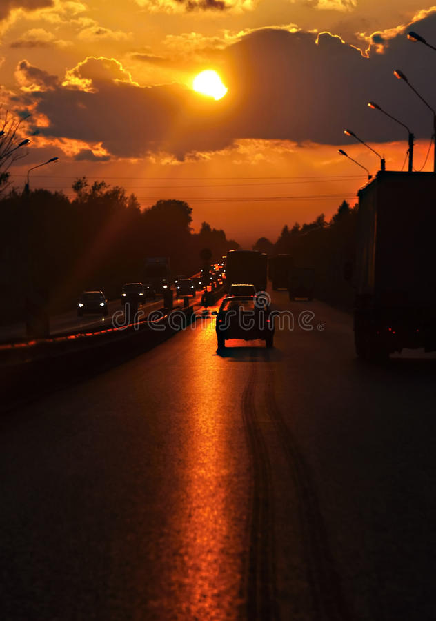 Highway cars driving into the sunset. Blur. The vertical frame royalty free stock images