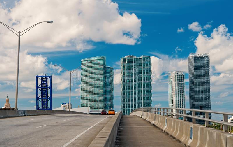 Highway with cars and skyscrapers of miami, usa. Road or roadway for transport traffic on cloudy blue sky. Public. Highway with cars and skyscrapers of mi, usa royalty free stock image