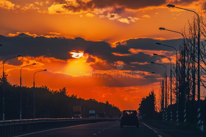 Highway with cars traveling on the sunset. Horizon line with the sun and storm clouds. Journeys. Selective focus.  royalty free stock image