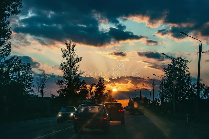 Highway with cars traveling on the sunset. Horizon line with the sun and storm clouds. Journeys. Selective focus.  royalty free stock images