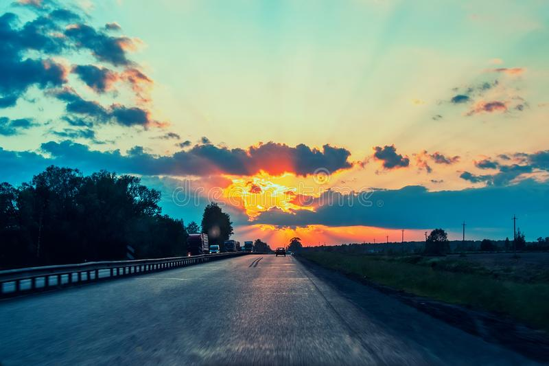 Highway with cars traveling on the sunset. Horizon line with the sun and storm clouds. Journeys. Selective focus.  stock photos