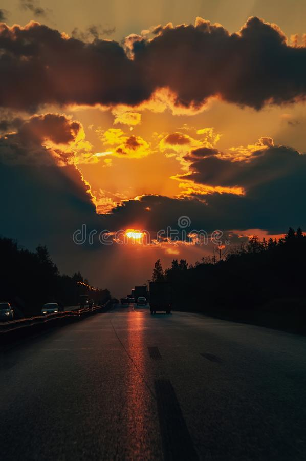 Highway with cars traveling on the sunset. Horizon line with the sun and storm clouds. Journeys. Selective focus.  royalty free stock photo