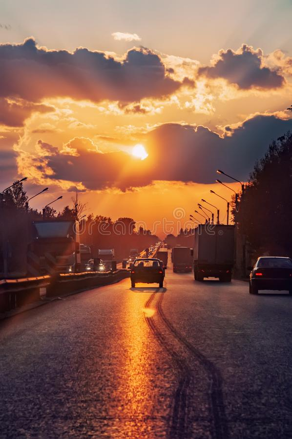 Highway with cars traveling on the sunset. Horizon line with the sun and storm clouds. Journeys. Selective focus. Highway with cars driving at sunset. Horizon royalty free stock photo