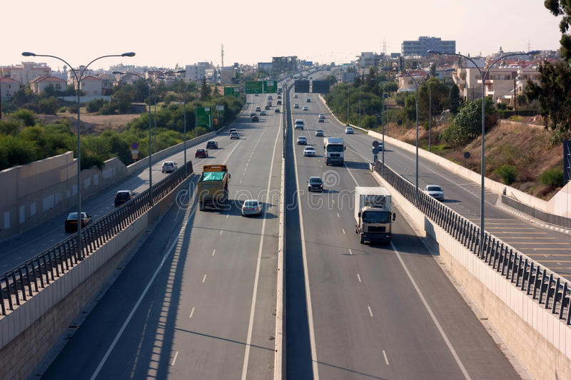 Highway with city in the distance. Image shows a highway with a city in the distance, populated by a couple of trucks and normal, family vehicles stock photo