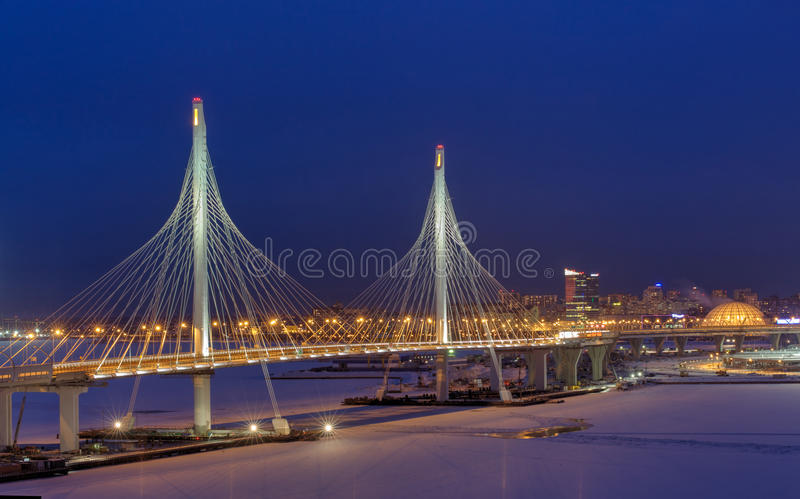 Highway crosses frozen river, stayed bridge at night illuminated. St. Petersburg, Russia - January 3, 2017: Express roads crosses the river icebound, guyed stock photos