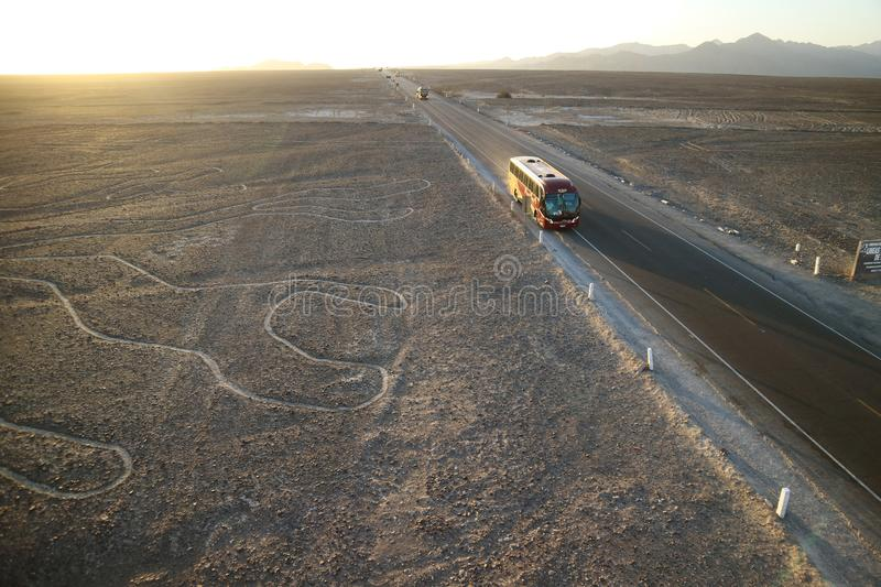 Highway cut through the famous large ancient geoglyphs Nazca lines as seen from the observation tower, Nazca desert of Peru. South America royalty free stock photos