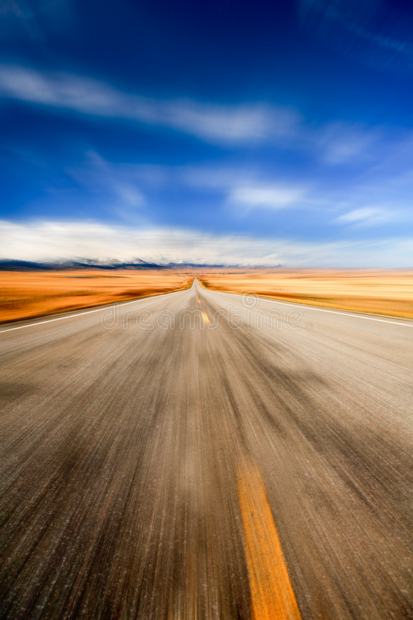 Highway through desert. Motion blue of deserted highway receding into distance through desert