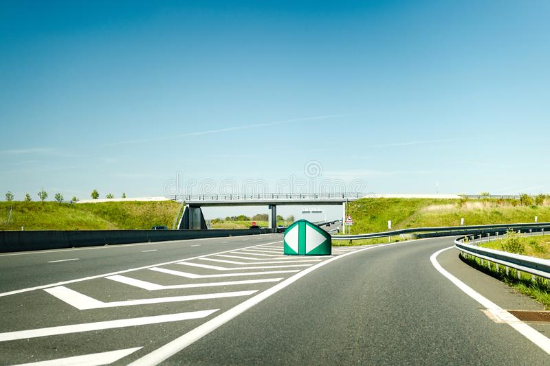 Highway exit - clear blue sky. French autoroute highway exit on the right with security differentiator and overpass - clear blue sky to great holidays stock image