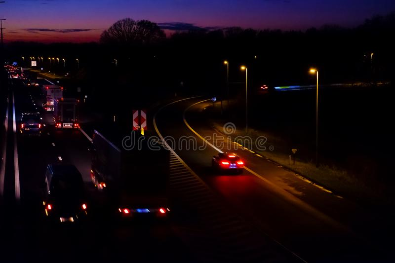 Highway with exit at sunset. Burning streetlights cars and trucks stock photography