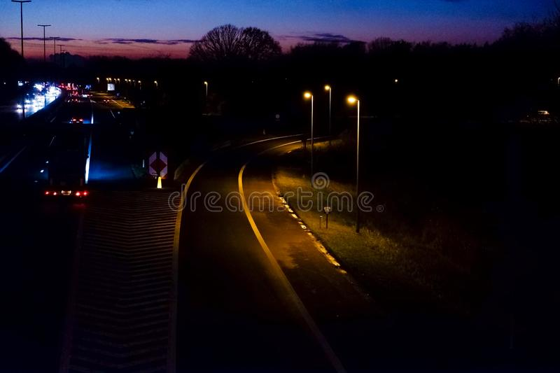 Highway with exit at sunset. Burning streetlights cars and trucks stock image