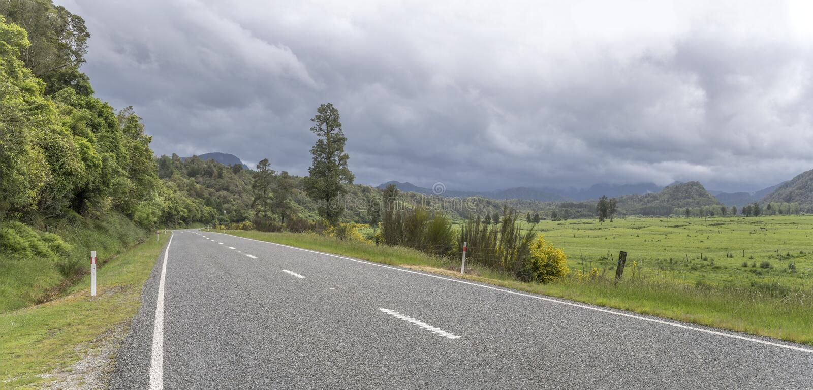 Highway 6 and green meadows under cloudy sky, near Inangahua Junction, West Coast, New Zealand. Landscape with highway 6 and green lush meadows under cloudy sky royalty free stock photos