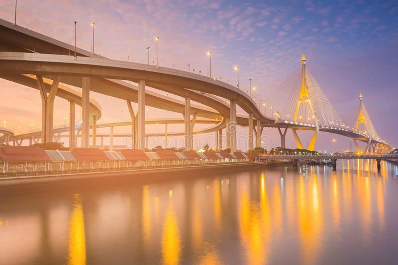 Highway intersection connect to twin suspension bridge over river. Water reflection light night view royalty free stock photography