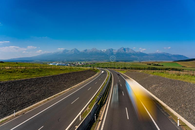 Highway leading to rocky peaks of High Tatras mountains. stock photos