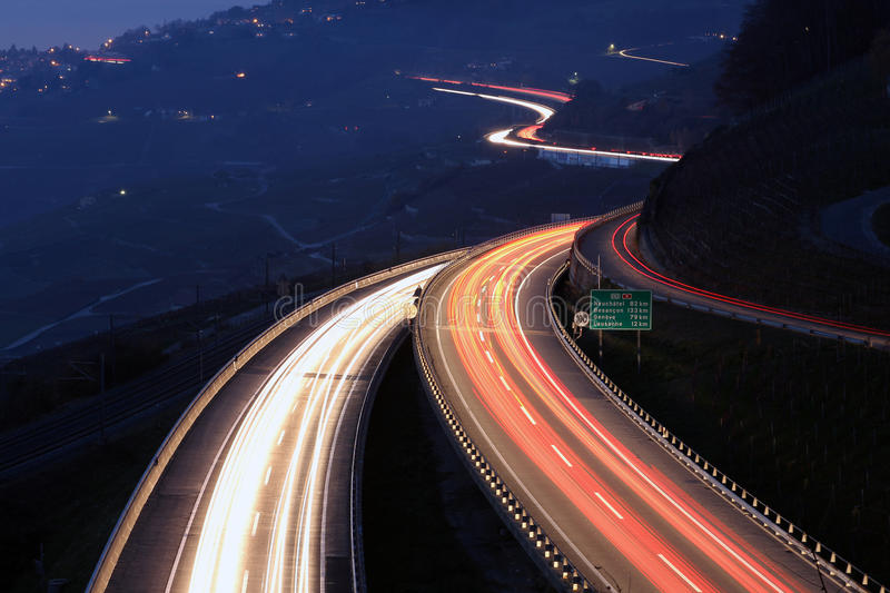 Highway at night. Traffic trail lights of the highway connecting Lausanne with Montreux, passing trough the world heritage wine region of Lavaux on the shore of royalty free stock photos