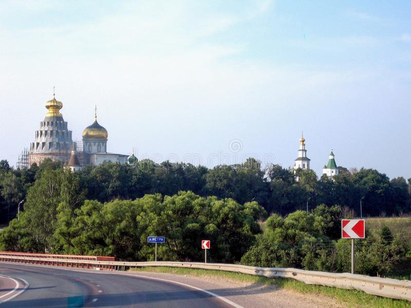 Highway past the monastery with a high temple on a Sunny day stock photography