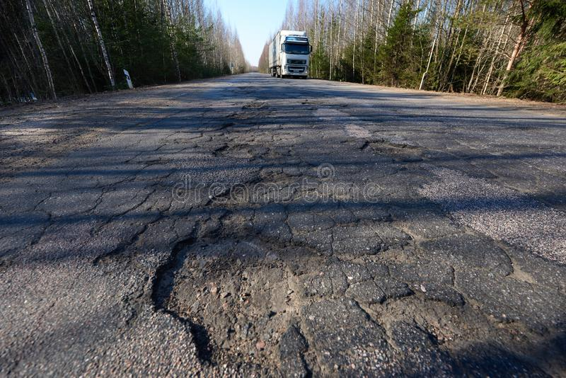 Highway with potholes. Poor quality pavement in the primary stage of its destruction. On the road car. Leningrad region, Russia - April 15, 2018: Highway with stock photo