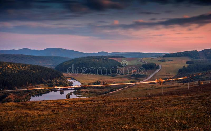 Highway and road bridge over the river at sunset evening sun on the background of the Mountains. stock photo