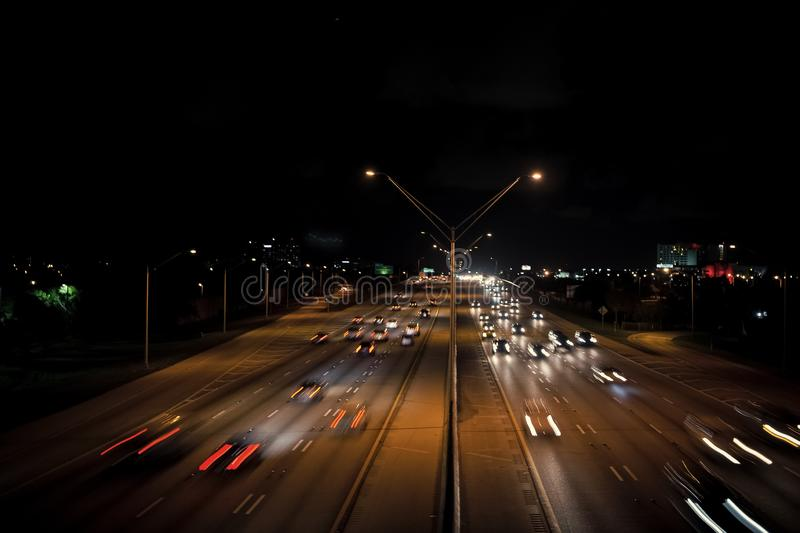 Highway road with car trails at night on dark sky stock photo