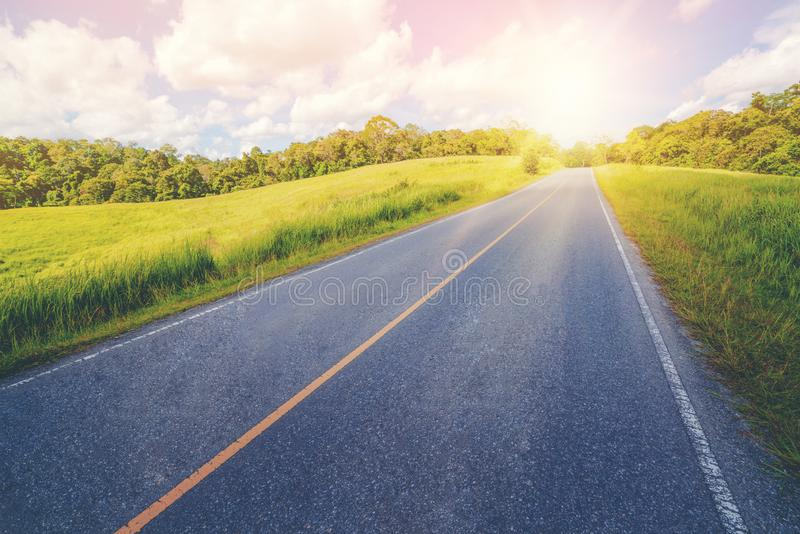 Highway road through green grass under blue sky. Highway road up hill through green grass field under white clouds on blue sky in summer day. Road trip travel stock image