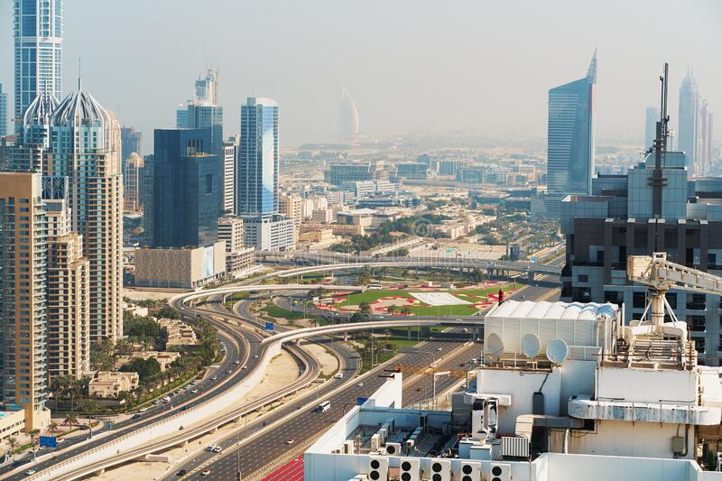 Highway road interchange or junction with urban car traffic and Dubai skyline with high tower buildings, UAE, view from. Above stock images