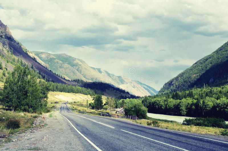 Highway road in a narrow mountain valley along the river, woodland and farm at sunset under a cloudy sky with blue clouds. Chuyskiy trakt Altai, Siberia, Russia royalty free stock photography