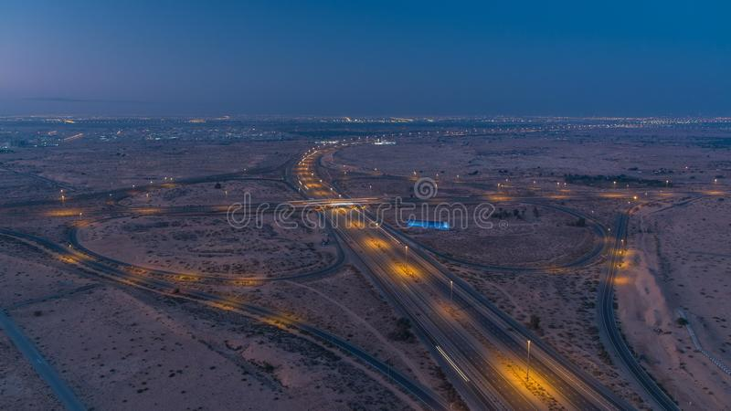 Highway roads with traffic night to day timelapse in a big city from Ajman to Dubai before sunrise. Transportation concept. royalty free stock photo