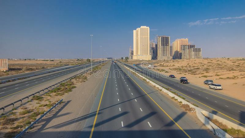 Highway roads with traffic timelapse in a big city from Ajman to Dubai before sunset. Transportation concept. royalty free stock photos