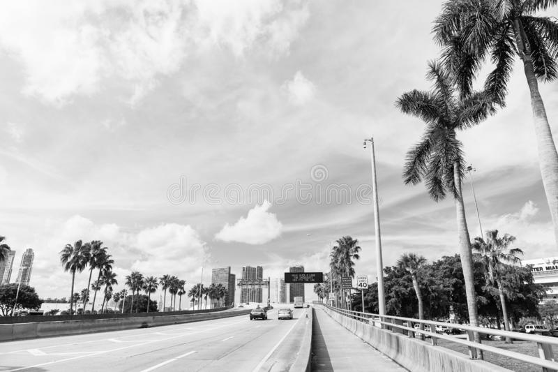 Highway or roadway with cars and skyline of miami, usa. Road with traffic signs for transport vehicles and palm trees on stock photo